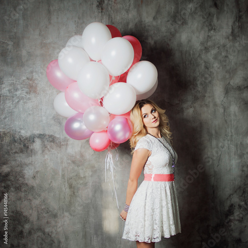 Charming young blonde in a white dress with pink sash, holding a large bundle of balloons at the party Poster
