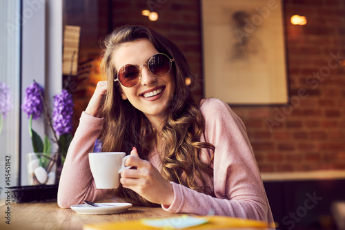 Happy woman drinking coffee at cafe
