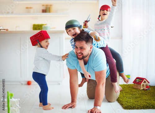 happy family playing together at home, riding on father