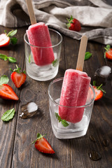 Glass with strawberry popsicles, strawberries and mint on old wooden background. Summer food concept