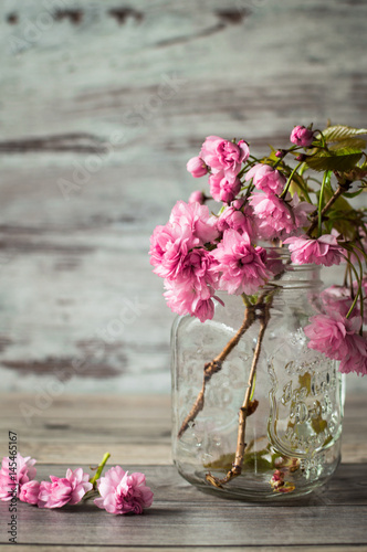 Poster The wonderful branches of pink flowering sakura in a glass jar with a handle