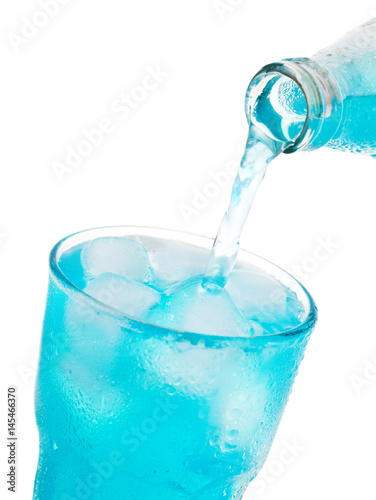 Poster pouring blue soda into glass with ice from bottle