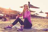 Young beautiful woman sitting on the beach and listen to music after jogging during sunset