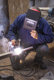 Welder in blue work suit connects two pieces of stainless steel with electric welding machine