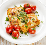 Grilled halloumi cheese with herbs and cherry tomatoes on a white plate