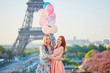 Two young women with bunch of balloons in Paris near the Eiffel tower