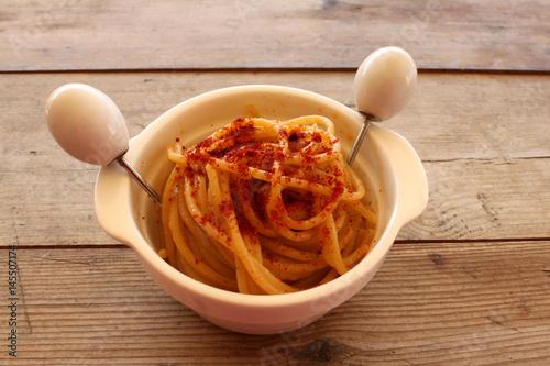 Poster pasta aglio,olio e peperoncino piccante in pentola bianca su tavolo di legno