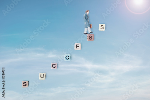 Papiers peints Positive Typography Success / Success. Motivational quote for life of alphabet cube on blue sky background with miniature toy of businessman walking.
