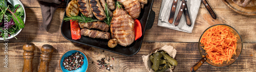 Grilled steak, grilled sausages, grilled vegetables on the wooden table - 145533359