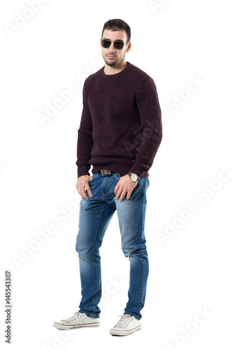 Poster Cool young man in sweater and sunglasses with hands in pockets looking at camera