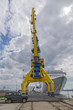 A high port crane in blue and yellow against the background of a dramatic sky and big white ship