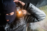 Policeman aiming pistol towards busted masked gangster at night - 145548307