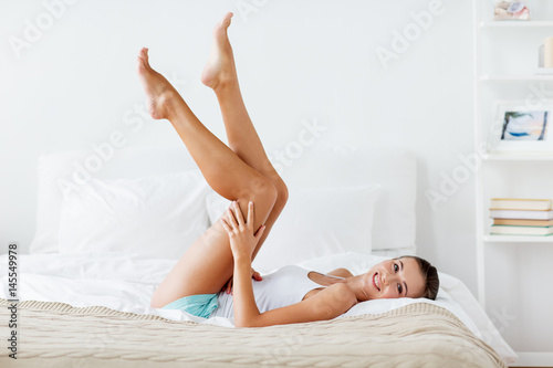 Foto Murales happy woman lying on bed and touching legs at home