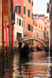 Gondola in narrow street with a canal, bridge and tourists in Venice