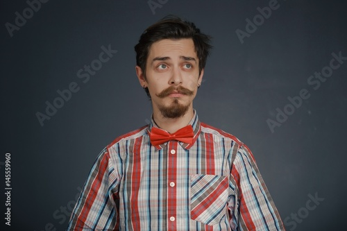Poster Young caucasian handsome hipster with beard posing in studio on dark background