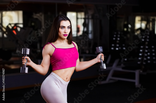 Young attractive muscular fitness woman doing exercise for triceps with dumbbell Poster