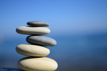Zen spa stones with blue water and sky. Balanced stones background, copy space. Spa symbol. Balancing stones. Symbol of stability. Tranquil, relaxation and health life. Stones balance. Sustainability.