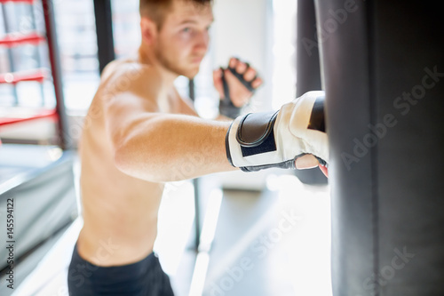 Portrait of shirtless muscular sportsman hitting punching bag during boxing prac