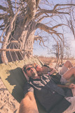 Couple taking selfie on hammock hanging from huge Baobab tree in the african savannah. Fisheye view, toned image. Wilderness safari and adventure in Africa.