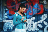 Young woman listening to music on her smart phone after jogging