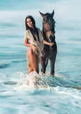 Sensual brunette lady walking with the majestic horse - 145624907