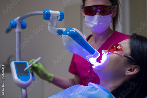 Fototapeta Close-up portrait of a female patient at dentist in the clinic. Teeth whitening procedure with ultraviolet light UV lamp.