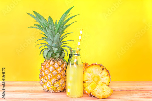 Canvas Sap The Bottles of pineapple juice with sliced pineapple fruit on wooden table with vibrant yellow background , summer fruit drink concept