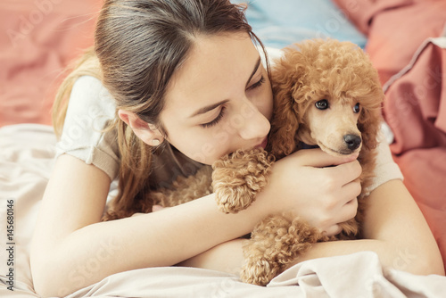 Plagát Young woman is lying and sleeping with poodle dog in bed.