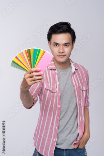 Young asian graphic designer holding color palette