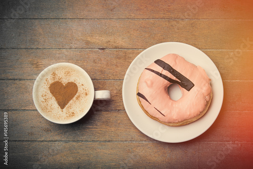Poster photo of glazed donut and cup of coffee on the wonderful brown wooden background