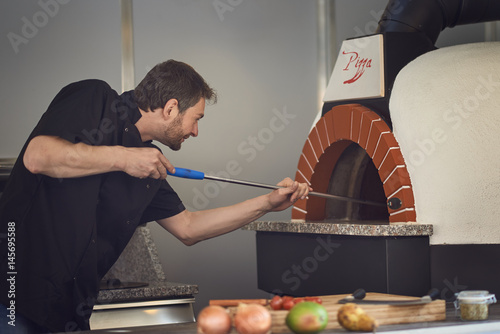 Fotobehang Pizzeria Chef einer Pizzeria mit Steinofen