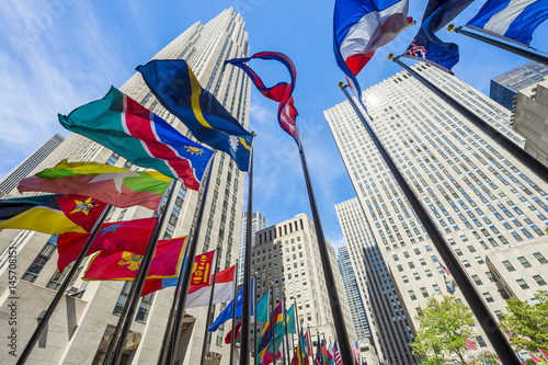 Colorful international flags fly in the breeze at the base of the traditional skyscrapers in New York City