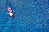 Enjoying suntan. Vacation concept. Top view of slim young woman in bikini and wide hat on the pink air mattress in the big swimming pool. - 145717914