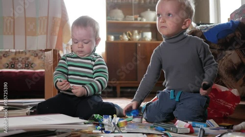 Two boys play at home with stationery. Cute brothers spend interesting time