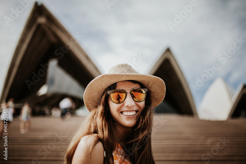 Cute smiling woman close up portrait, with Sydney Opera House building in the background Poster