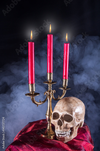 Papiers peints Table preparee ein Schädel aus Keramik, Kerzen und Nebel symbolisieren Tod und Trauer