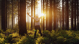Happy young man raised hands at sunset in the woods