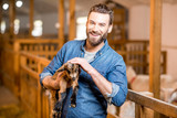 Handsome farmer taking care of cute goat baby at the barn - 145749357