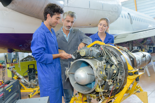 Students and teacher looking at aircraft turbine