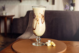 Chocolate banana milkshake in the glass hurricane on the table