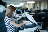 Businesswoman using copy machine in office - 145774944