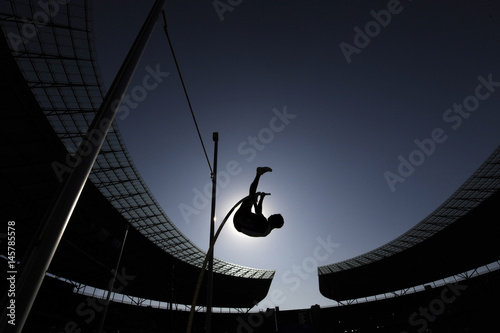 Juliste A pole vaulter is silhouetted against the sun during an athletics competition