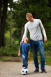 Modern dad and little boy playing in  park