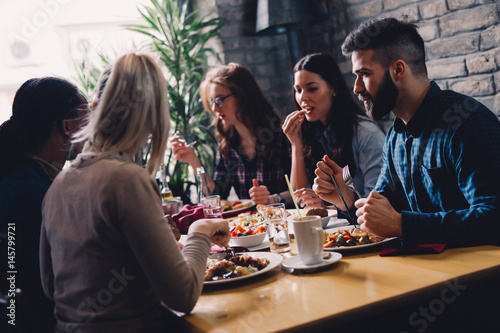 Group of happy business people eating in restaurant