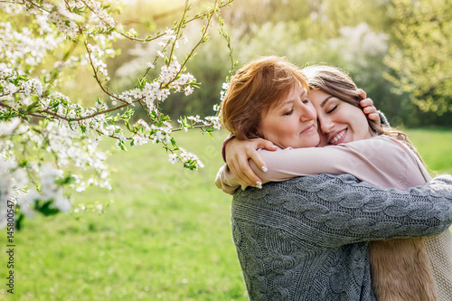 Middle-aged mother and her daughter hugging in blooming garden