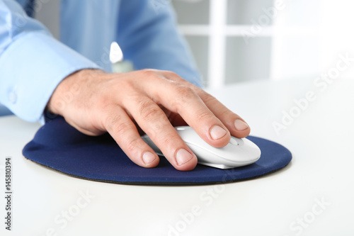 Hand of man working with computer mouse in office Poster