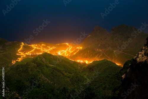 night view from Mirador de Jardina, Parque Rural de Anaga, northern Tenerife, Spain. The city below the mountain is illuminated and looks like burning fire in the foggy night