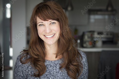 Portrait Of A Mature woman smiling At The Camera. In the kitchen. Poster