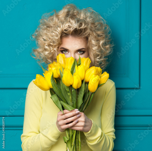 Beautiful blonde girl in yellow shirt with flowers tulips in hands on a turquoise background