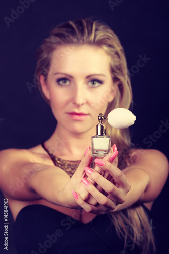 Beautiful woman with necklace holding perfume